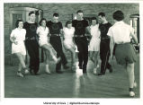 Chorus line practicing kicks, The University of Iowa, 1940s
