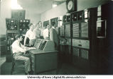 WSUI employees examining station equipment, The University of Iowa, 1940s