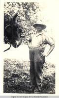 John Heitzman with horse in hayfield