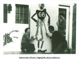 Students painting design on building for Homecoming, The University of Iowa, 1940s