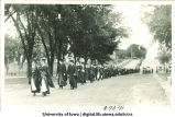 Women holding flowers leading commencement procession down Washington St., The University of Iowa, 1910s