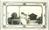 Women wearing hats sitting at train depot, Donnellson, Iowa, 1910s