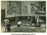 Students painting modern art wall hanging, The University of Iowa, March 4, 1940