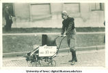 Student dressed as football player pushing baby carriage for Mecca Day parade, The University of Iowa, 1921