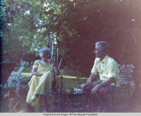 Elizabeth, Bill and corgy sit on patio outside sun porch