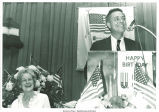 Sen. James Buckley at podium with Mary Louise Smith laughing, Nassau County fund-raising dinner, Hauppauge, N.Y., June 19, 1975