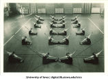 Students in gymnasium doing floor exercises, The University of Iowa, 1930