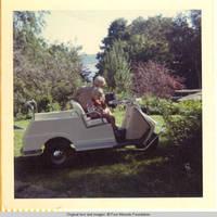 Unknown man and John, Jr. in golf cart near Rock garden
