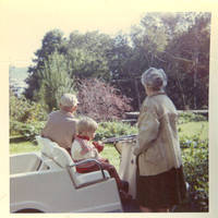 Unknown man and woman with John, Jr. in golf cart facing rock garden