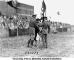Woman accepting colors from cadet during Governor's Day ceremony, The University of Iowa, 1929