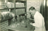 Student performing lab experiment, The University of Iowa, 1920s?