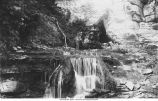 Man standing at top of waterfall in Devil's Den, Iowa, late 1890's or early 1900s