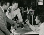 Three men work with scientific apparatus in the Farm Machinery Lab, 1957