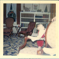 John, Jr. standing in the parlor by chair