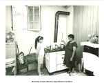 Virginia and Julia Guzman in kitchen, Cerro Gordo County, Iowa, 1960s
