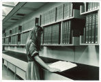 Woman reading National Union Catalog volume in Main Library, the University of Iowa, 1970s