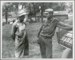 Two men talking by a piece of farm equipment