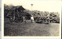 George A. Burden and Vidie Burden with push mower by Four Mounds well
