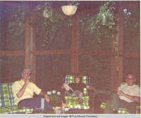 Bill smoking cigarette, John, Jr. and unknown man relaxing in screened in porch