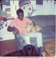 Ainsley Benard sitting on couch with Victoria in his lap and Sadie at his feet at White house