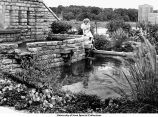 Woman with fountain near Iowa Memorial Union Pedestrian Bridge, Iowa City, Iowa, between 1936 and 1939