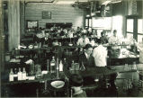 Students at workstations in pharmacy laboratory, The University of Iowa, 1930s