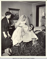 Unknown woman and Frindy lifting her skirts to corgies in parlor
