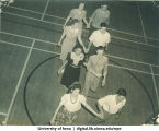 Couples walking across gymnasium hand in hand, The University of Iowa, 1940s