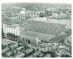 Aerial view of football stadium with arched Armory and Field House behind, the University of Iowa, March 1953