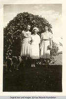 Three women by lilac bush