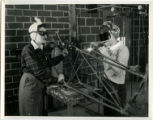 Two cadettes welding parts of the tail of a wrecked plane, 1943