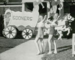 Two girls are posed in front of a covered wagon lawn display at Homecoming, 1946