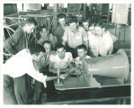 Aerodynamics class examining a model plane, The University of Iowa, 1940s