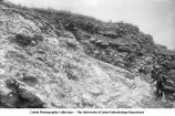 Man standing by oblique bedding in Sugar Creek lime quarries, Sugar Creek, Iowa, late 1890s or early 1900s