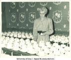 Woman lighting candles on cakes, Centennial Dinner, Iowa Memorial Union, University of Iowa, February 25, 1947