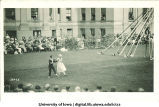 Women in costume dancing on the Pentacrest lawn near maypole for audience, The University of Iowa, June 1924