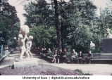 People on park benches by statue, Siberia, 1944