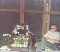 John, Jr. and unknown man sitting in screened in porch