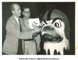 Arnold Gillette and Joy Anderson with new helmeted Herky head before it travels to the Rose Bowl, The University of Iowa, December 27, 1956