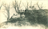 Women sitting on large haystack, Iowa, March 12, 1908
