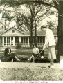Students on benches near the clubhouse watch a classmate get ready to drive the golf ball, The University of Iowa, 1950s