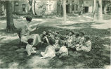 Woman reading to small children outside, The University of Iowa, 1920s
