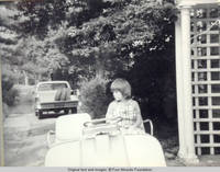 John, Jr. sitting in golf cart looking rt, near trellis and front entrance
