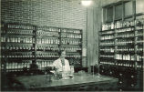 Student surrounded by compounds and equipment in pharmacy laboratory, The University of Iowa, 1930s