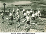 Students standing on dock holding oars horizontally, The University of Iowa, 1930s