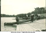 Students launching a canoe from a dock, The University of Iowa, 1928?