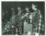 Scottish Highlander Barbara Brewer introducing alternate drum major Kathy Monahan at banquet, The University of Iowa, 1968?