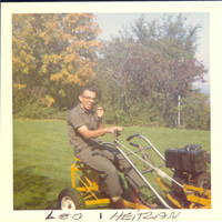 Leo Heitzman on lawn mower, smoking a pipe