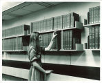 Woman with National Union Catalog volumes in Main Library, the University of Iowa, 1970s