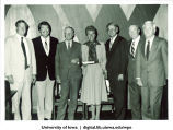 Christine Grant, football coach Hayden Fry, and other men from the athletics department, The University of Iowa, 1970s